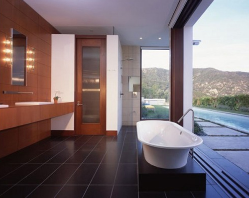 mid-century-modern-bathroom-design-with-open-plan-and-stunning-white-tub-on-black-tile-floor-before-long-wooden-vanity-idea-with-frameless-wall-mirror-and-wooden-backsplash