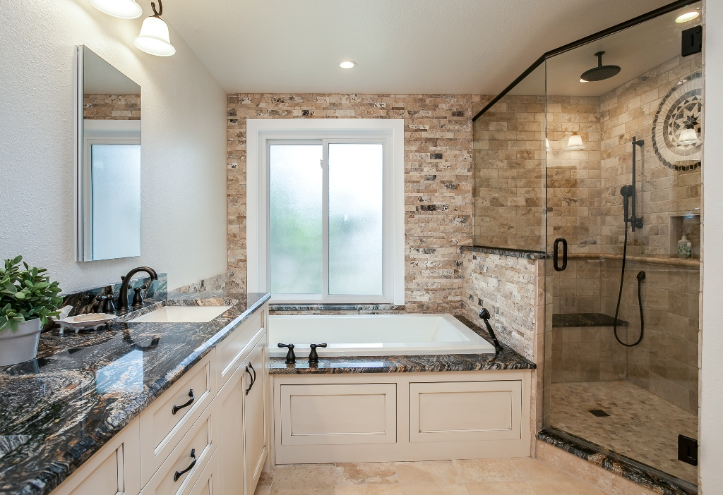 Bathroom surrounded with polished granite along with bathtub and shower.