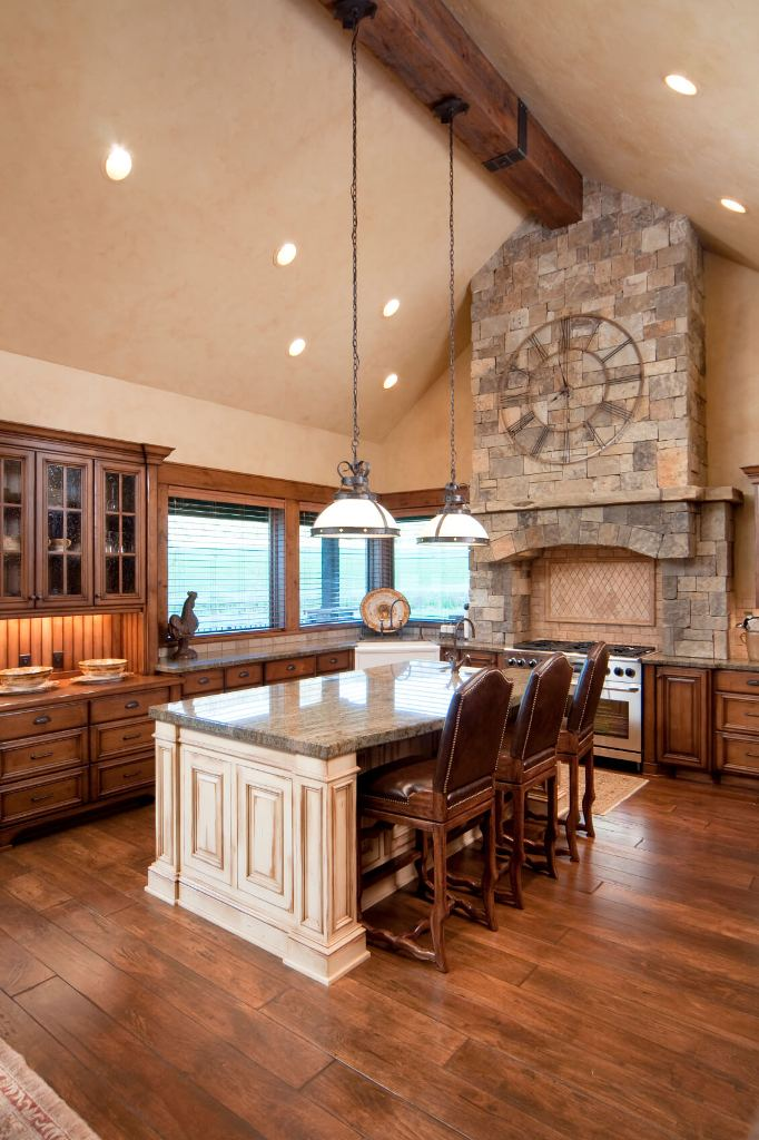 This kitchen is flush with warm natural wood tones, natural stone wall above the range